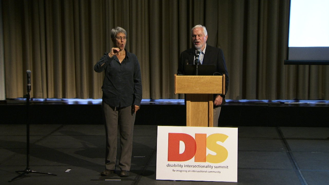 Photo of speakers at podium at the DIS.