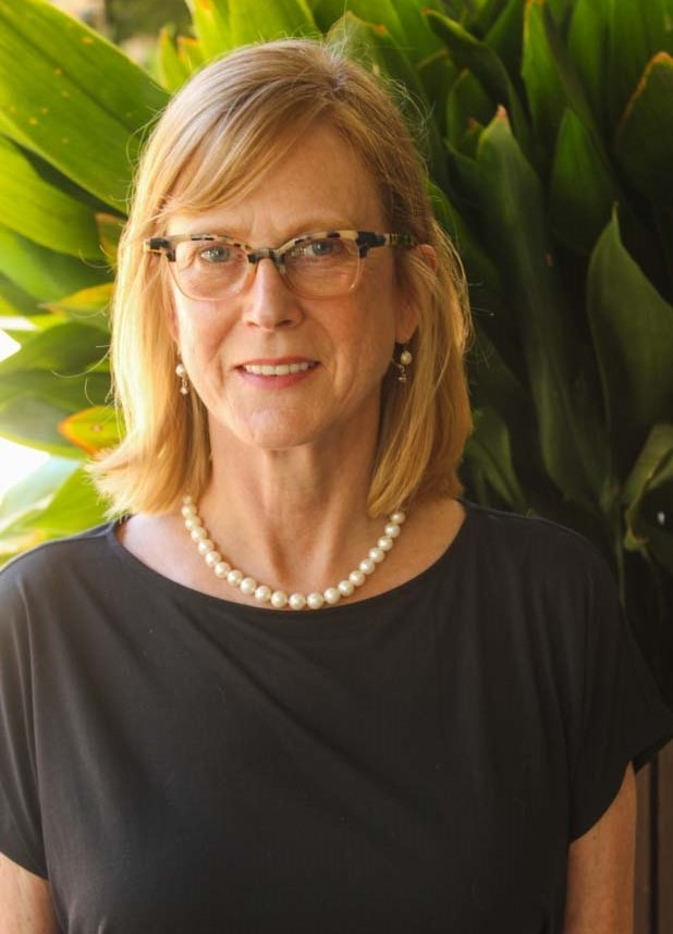 Amy Sharp, Ph.D. headshot smiling wearing glasses, a pearl necklace, and a black blouse against a leafy background.